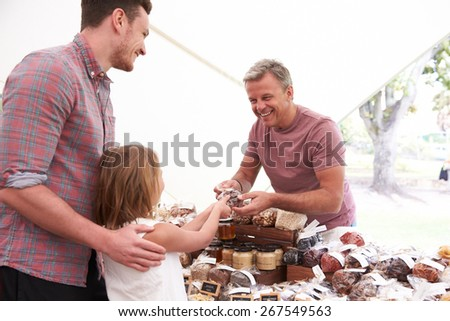 Family Buying Nuts From Stall At Farmers Market - stock photo