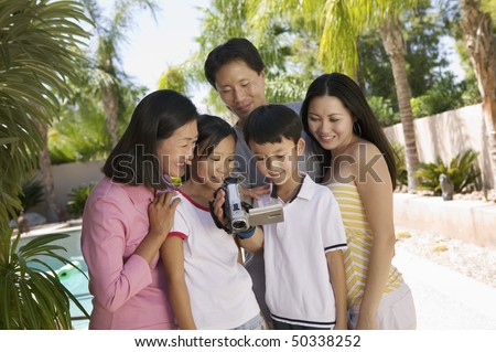 Family by pool in backyard Looking at Video Camera Screen, front view - stock photo