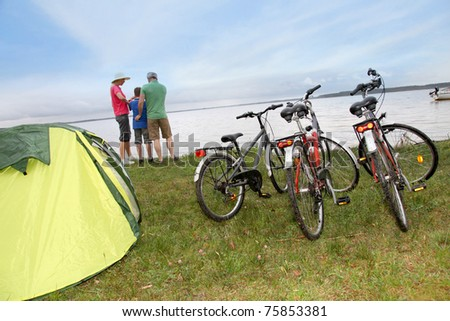 Family camping by a lake - stock photo