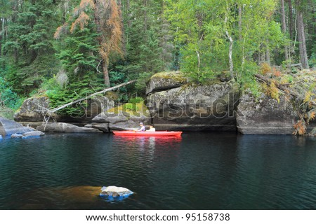 Family canoeing in a beautiful remote lake - stock photo