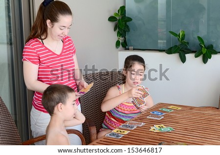 Family card game - teenage sisters and their younger brother playing a game of cards - stock photo