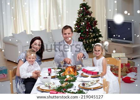 Family celebrating Christmas dinner with turkey against snow - stock photo