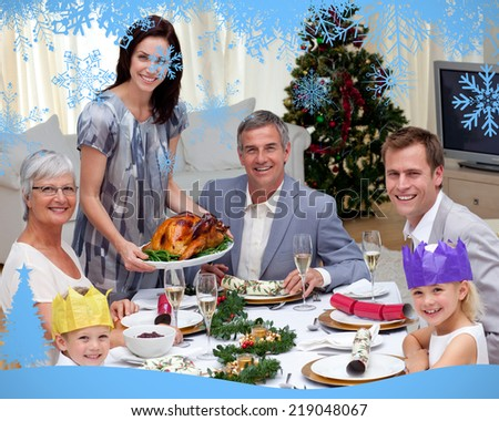 Family celebrating Christmas dinner with turkey against snow flake frame in blue - stock photo