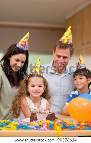 Family celebrating daughters birthday together - stock photo