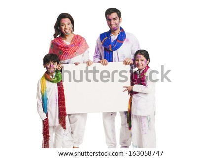 Family celebrating Holi and holding a blank placard - stock photo