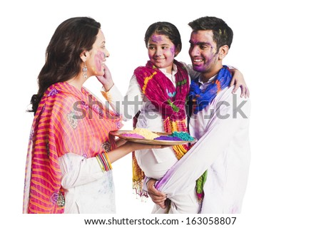 Family celebrating Holi festival - stock photo
