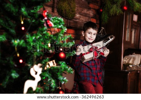 Family celebration of the New Year. Boy near a Christmas tree. Giving gifts. Holiday and fun. - stock photo
