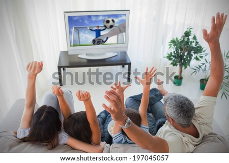 Family cheering and watching the world cup at home in the living room - stock photo