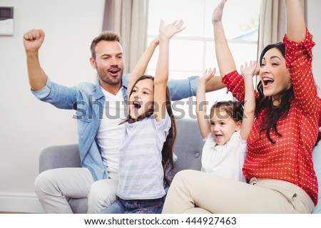 Family cheering while sitting on sofa at home - stock photo