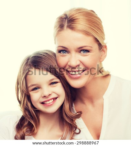 family, child and home concept - smiling mother and little girl at home - stock photo