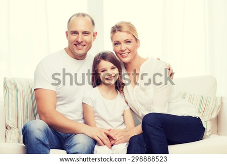 family, child and home concept - smiling parents and little girl at home - stock photo