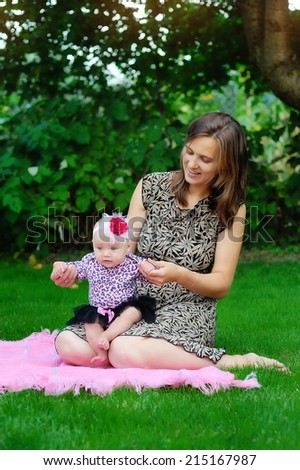 family, child and parenthood concept - happy mother holding and raising little baby up in park  - stock photo