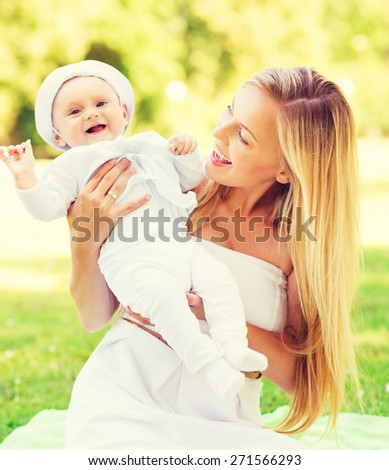 family, child and parenthood concept - happy mother with little baby sitting on blanket in park - stock photo