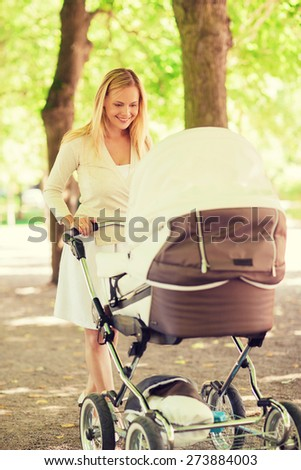 family, child and parenthood concept - happy mother with stroller in park - stock photo