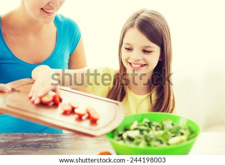 family, child, cooking and home concept - smiling little girl with mother adding tomatoes to salad in the kitchen - stock photo