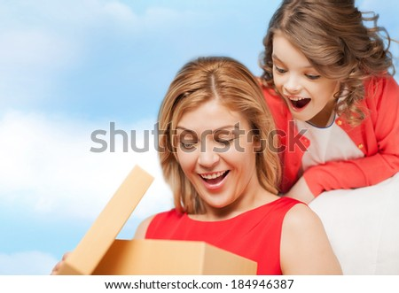 family, child, holiday and party concept - smiling mother and daughter with gift box - stock photo