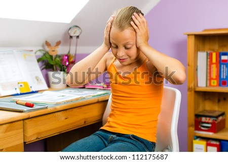 Family - child sitting at home at her desk and doing homework and she does not have much fun - stock photo