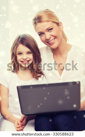 family, child, technology and home concept - smiling mother and little girl with laptop at home - stock photo