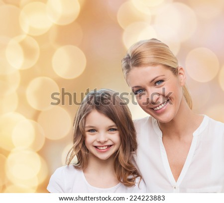 family, childhood, happiness and people - smiling mother and little girl over beige lights background - stock photo