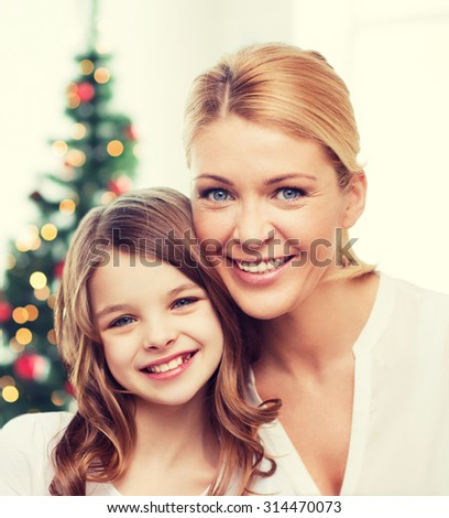 family, childhood, holidays and people - smiling mother and little girl over christmas tree background - stock photo