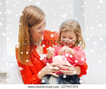 family, childhood, holidays, finances and people concept - happy mother and daughter with piggy bank - stock photo