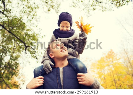 family, childhood, season and people concept - happy father and son having fun in autumn park - stock photo