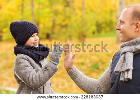 family, childhood, season, gesture and people concept - happy father and son making high five in autumn park - stock photo