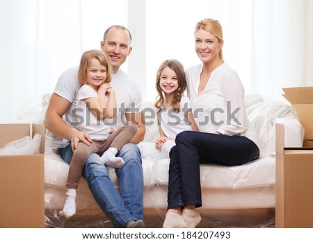 family, children, accommodation and home concept - smiling parents and two little girls moving into new home - stock photo