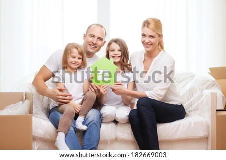 family, children, accomodation and home concept - smiling parents and two little girls holding green house - stock photo