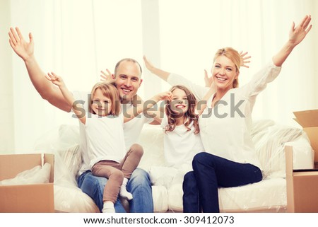family, children, accomodation and home concept - smiling parents and two little girls waving hands at new home - stock photo