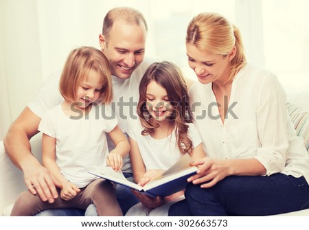 family, children and home concept - smiling family and two little girls with book at home - stock photo