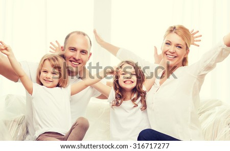 family, children and home concept - smiling parents and two little girls at home waving hands - stock photo