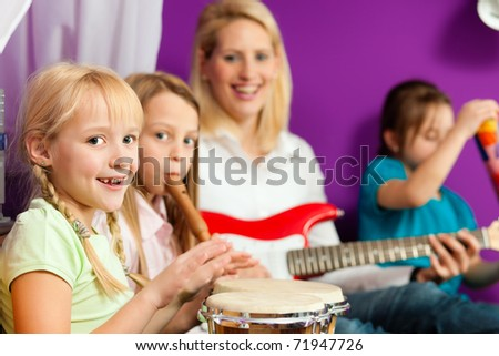 Family - Children and mother - making music; they are practicing playing guitar, bongo and flute - stock photo