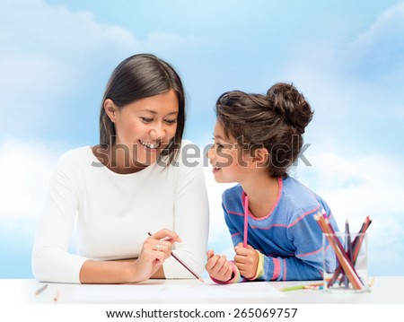 family, children and people concept - happy mother and daughter drawing and talking over blue sky background - stock photo