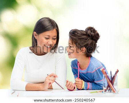 family, children and people concept - happy mother and daughter drawing and talking over green background - stock photo