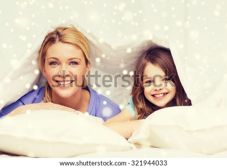 family, children, comfort, bedding and home concept - happy mother and girl under blanket over snowflakes background - stock photo
