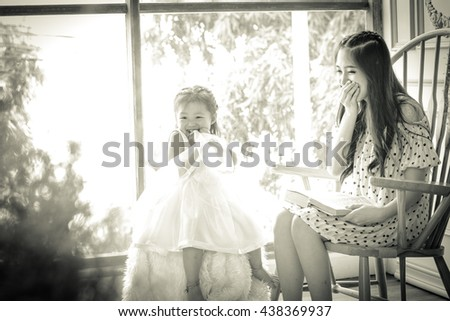 family, children, education, school and happy people concept - happy mother and daughter reading book .Backlit shot ,Picture is black and white - stock photo
