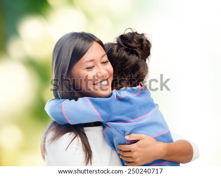 family, children, love and happy people concept - happy mother and daughter hugging over green background - stock photo