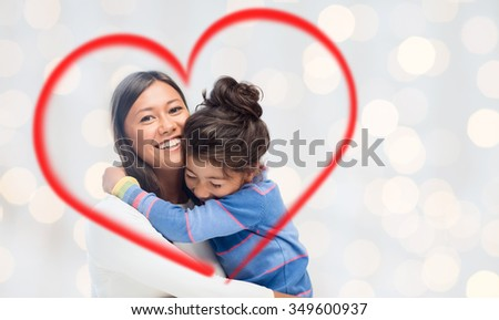 family, children, love and happy people concept - happy mother and daughter hugging over holidays lights background and red heart shape - stock photo