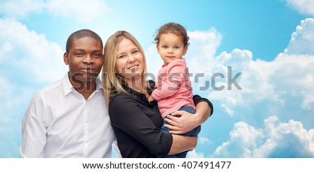 family, children, race and international concept - happy multiracial mother, father and little child over blue sky and clouds background - stock photo