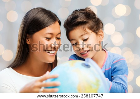 family, children, travel, geography and happy people concept - mother and daughter with globe over holidays lights background - stock photo