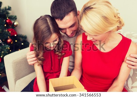 family, christmas, holidays, happiness and people concept - happy family opening gift box - stock photo