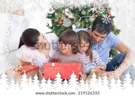 Family Christmas portrait against fir tree forest and snowflakes - stock photo
