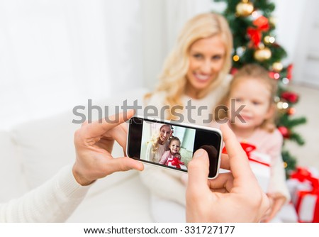 family, christmas, technology and people concept - close up of man taking picture of his family by smatrphone - stock photo