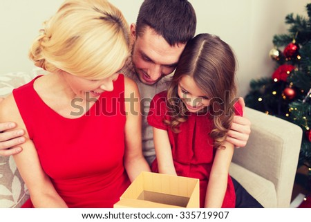 family, christmas, winter holidays, happiness and people concept - happy family opening gift box - stock photo