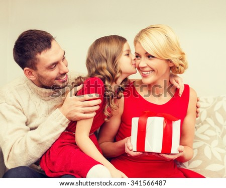 family, christmas, x-mas, happiness and people concept - adorable child kisses her mother and gives present - stock photo