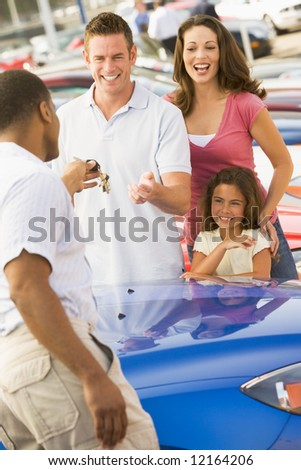 Family collecting new car from dealer - stock photo
