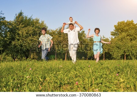Family Concept and Ideas. Happy Family of Four Running Together Outside in Green Summer Forest. Horizontal Image Orientation - stock photo