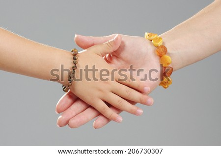 Family concept : mother and daughter hands together - stock photo