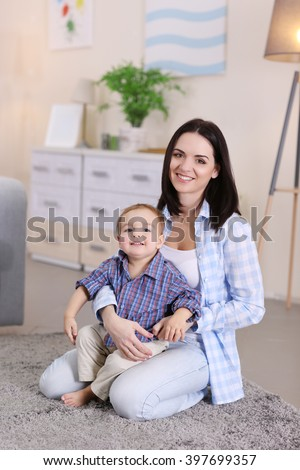Family concept. Mother  with son are playing in the room - stock photo